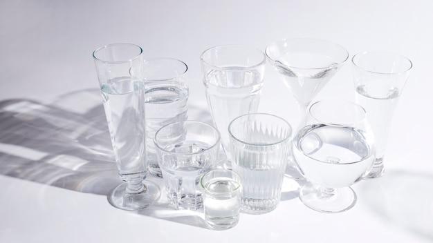Water in ander soort glazen met schaduw op witte achtergrond Gratis Foto
