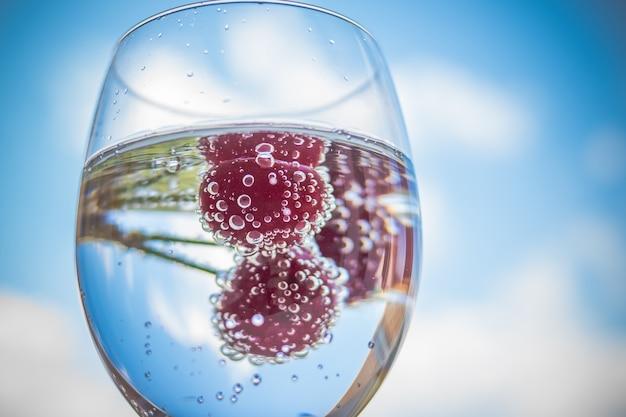 Water met vers fruit en glazen servies. cocktails met rijpe zoete rode kers. limonade, zomerse drankjes. glas limonade-ijswater Premium Foto