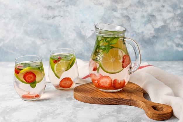 Water met verse limoen, aardbeien en mint, cocktail, detoxdrank, limonade. zomer drankjes. gezondheidszorg concept. Gratis Foto