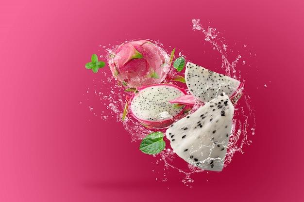 Water spatten op dragon fruit of pitaya over roze achtergrond Premium Foto
