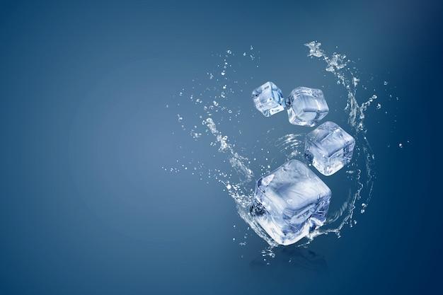 Water spatten op ijsblokjes geïsoleerd over een blauwe achtergrond en kopie ruimte Premium Foto