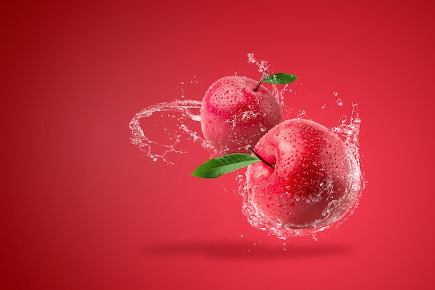 Water spatten op verse rode appel op rode achtergrond. Premium Foto