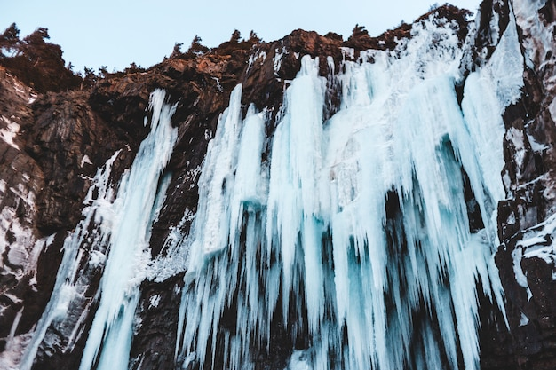 Water valt overdag op bruine rotsachtige berg Gratis Foto