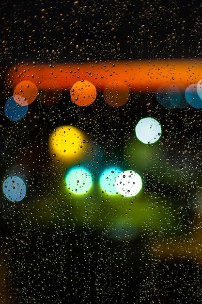 Waterdaling bij vensters en bokeh van stad in zonsondergang Premium Foto