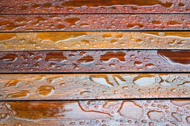 Waterdalingen op een houten vloeroppervlakte druppel water op hout met regendruppel na een regen. Premium Foto