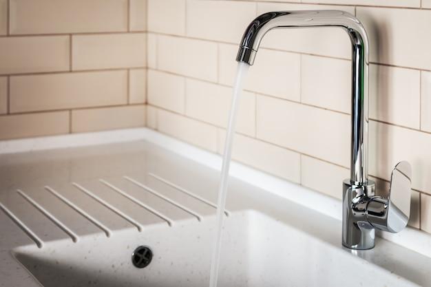 Waterkraan in de keuken. water stroomt uit de kraan Premium Foto