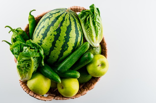 Watermeloen in een rieten mand met sla, appel, komkommer, avocado, paprika op een witte tafel Gratis Foto