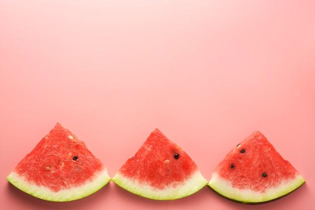 Watermeloen plakjes roze achtergrond Premium Foto