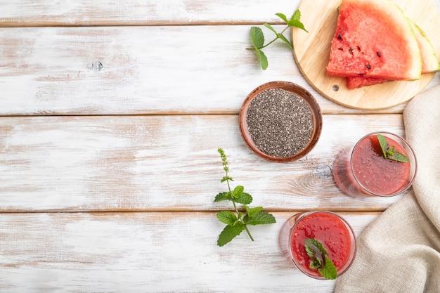 Watermeloen sap met chiazaadjes en munt in glas op een witte houten achtergrond met linnen textiel. gezond drankje concept. bovenaanzicht, kopie ruimte, plat leggen. Premium Foto