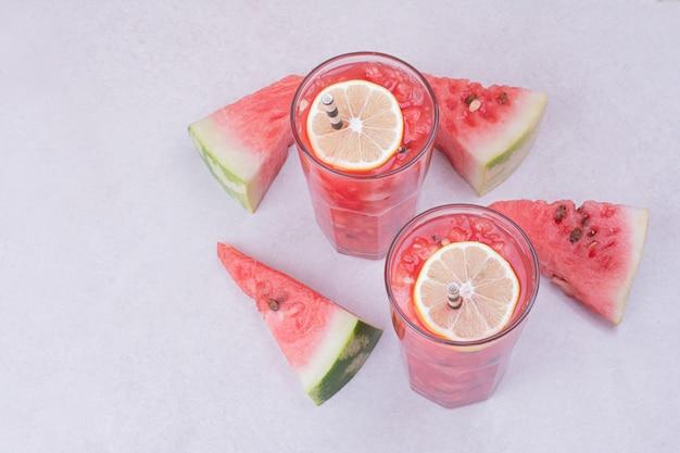 Watermeloen sap met plakjes rood fruit op wit. Gratis Foto