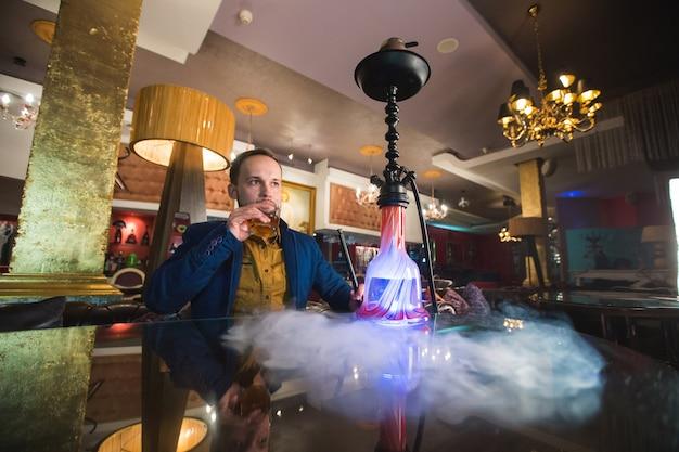 Waterpijp roken. de mens blaast rook. â â Premium Foto