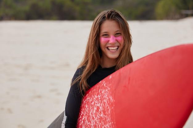 Watersport concept. gelukkig opgetogen surfboarder in duikpak Gratis Foto