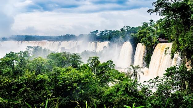 Waterval in iguazu national park omgeven door bossen bedekt met de mist onder een bewolkte hemel Gratis Foto