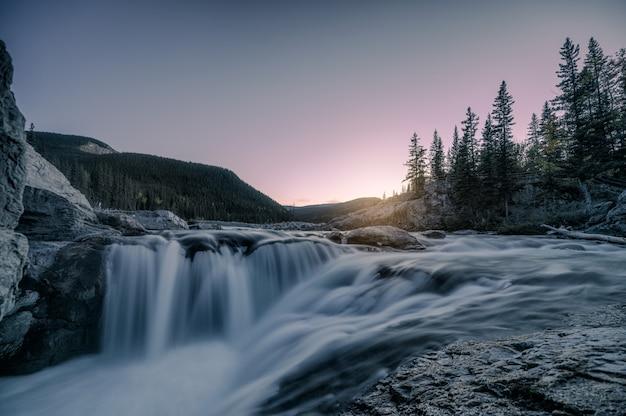 Watervalstroomversnelling die op rotsen in bos op avond stromen Premium Foto