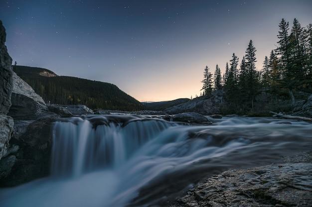Watervalstroomversnelling die op rotsen in pijnboombos stromen op avond bij elleboogdalingen Premium Foto