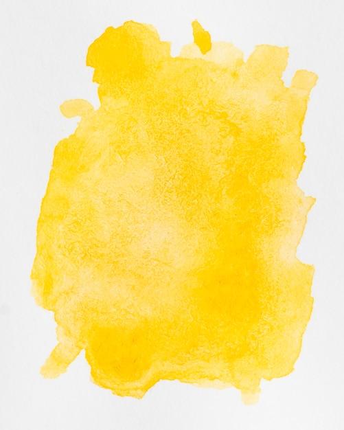 Waterverf vloeibare gele plonsen op witte achtergrond Gratis Foto