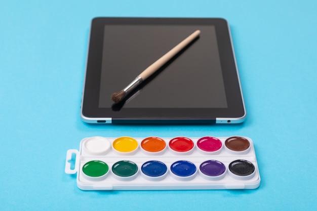 Waterverfverven en borstel die op tablet liggen die op blauwe achtergrond wordt geïsoleerd Premium Foto