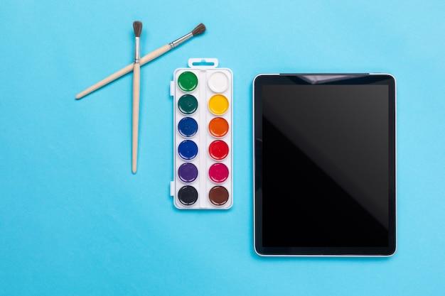 Waterverfverven en borstel met tablet op blauw Premium Foto