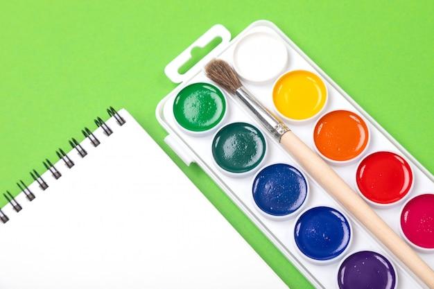 Waterverfverven en borstels met canvas voor het schilderen met copyspace op groen Premium Foto