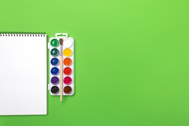 Waterverfverven en borstels met canvas voor het schilderen met copyspace op groene achtergrond Premium Foto