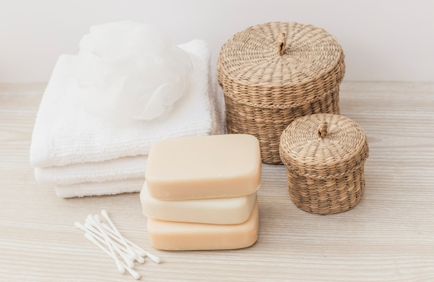 Wattenstaafje; zepen; handdoek; luffa en rieten mand op houten tafelblad Gratis Foto