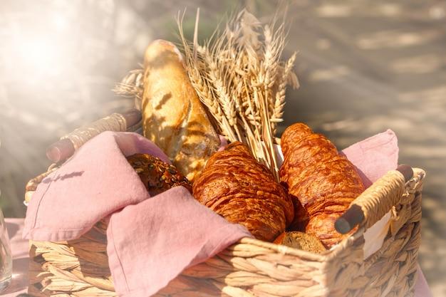 Wattledmand met broodcroissant en tarwe buiten in zonnige de zomerdag Premium Foto