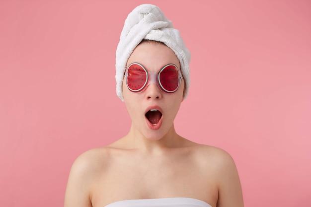 Wauw! cool nieuws! jong blij verbaasd meisje na spa met een handdoek op haar hoofd en masker op de ogen, met wijd open mond en ogen, hoort cool nieuws, staat. Gratis Foto