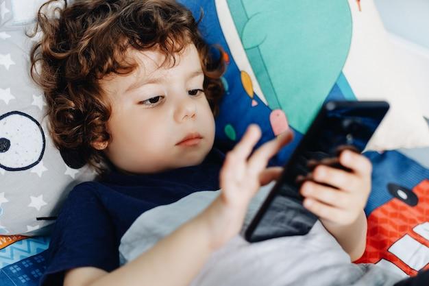 Wauw, ik vind die telefoon leuk. baby met smartphone. jongenszitting in bed en het spelen met mobiele telefoon. mijn moeder bellen. schattige kleine baby houdt mobiele telefoon in zijn handen en aandachtig kijken naar scherm. Premium Foto