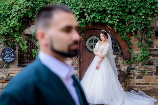 Wazig bruidegom op de voorgrond en een aantrekkelijke kaukasische bruid op de achtergrond buiten in de buurt van de houten deur bedekt met klimop Gratis Foto