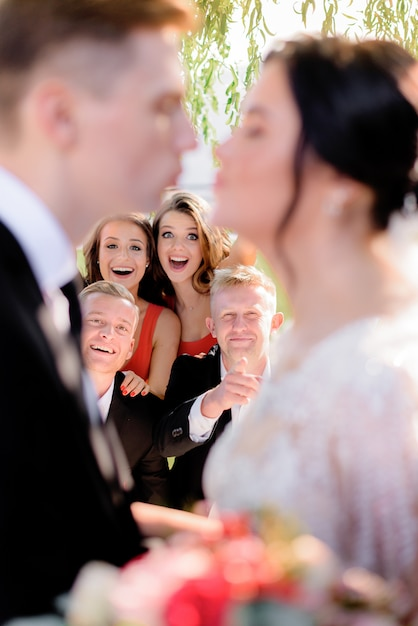 Wazig bruidspaar met gelukkig glimlachte gasten op de achtergrond buiten Gratis Foto
