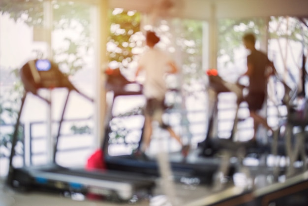 Wazig fitnesscentrum met cardio-apparaten en apparatuur voor krachttraining. cijfers van mensen die op loopbanden in de sportschool lopen. Premium Foto