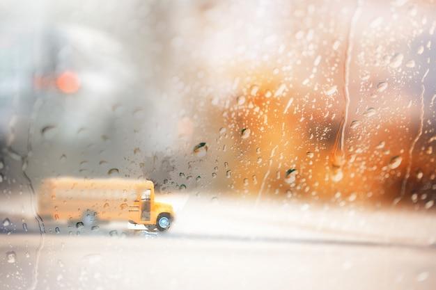 Wazig gele schoolbus, uitzicht door het raam op regenachtige dag. Premium Foto