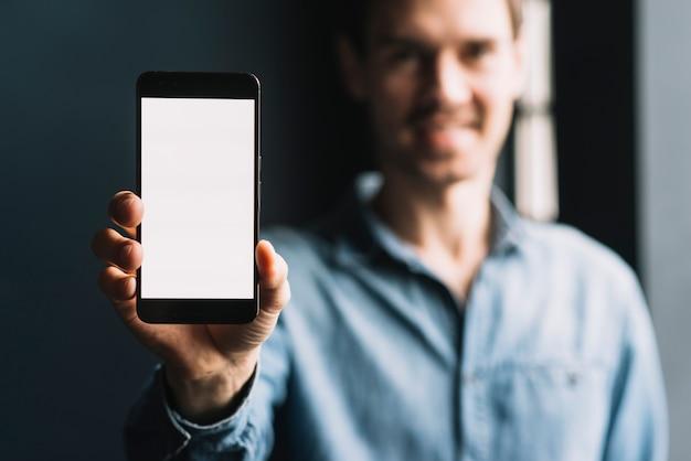Wazig jonge man blijkt smartphone met leeg wit scherm Gratis Foto
