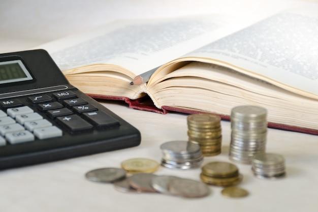 Wazig munten in stapels en een rekenmachine. het concept van hoge opleidingskosten voor de inwoners van arme landen Premium Foto