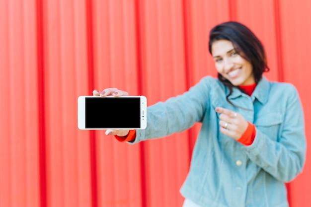 Wazig vrouw wijzend naar leeg scherm mobiele telefoon Gratis Foto