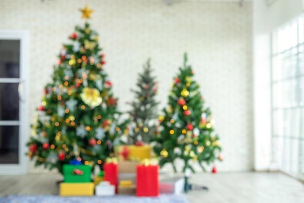 Wazig zicht op de kerstboom met rode geschenken. decoratie tijdens kerstmis en nieuwjaar. Premium Foto