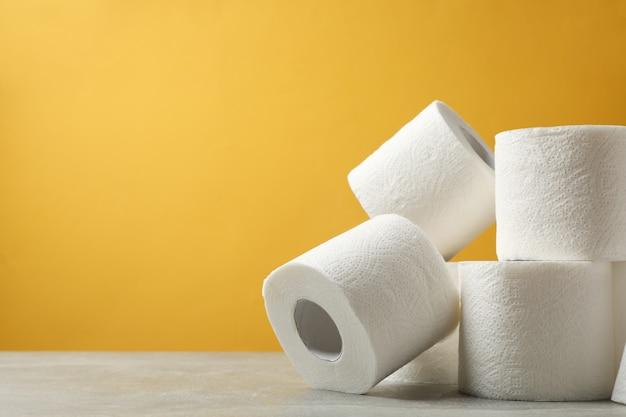 Wc-papier tegen gele tafel Premium Foto