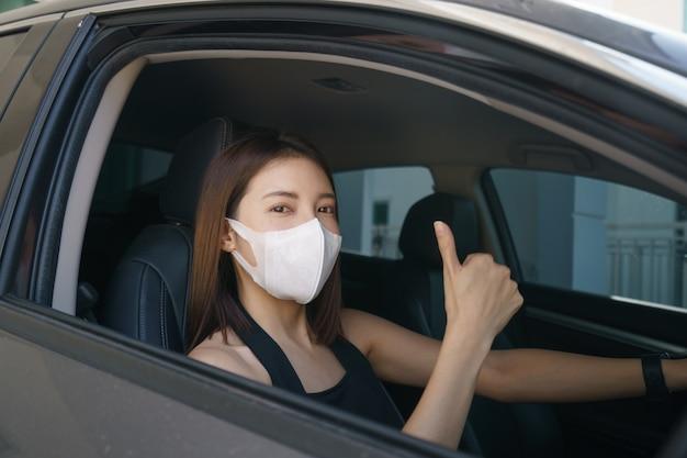 We dragen een chirurgisch masker in de auto, voor coronavirus of covid-19-bescherming. Premium Foto
