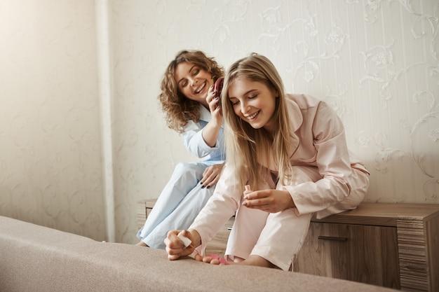 Weekend doorbrengen met zus is beter dan alleen. charmante gelukkige vrouw met krullend haar in pyjama die het haar van haar vriendin kamt terwijl ze vingernagels op voeten schildert, lacht en praat over het leven Gratis Foto