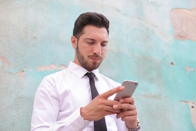 Weergave van een blanke man die op zijn telefoon speelt terwijl hij voor een groene muur staat Gratis Foto