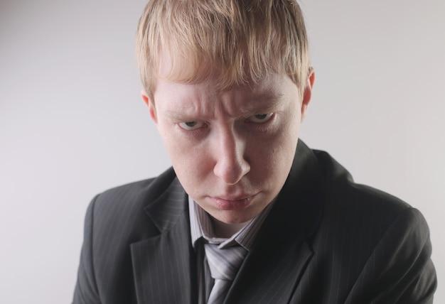 Weergave van een man in een donker pak met een boze gelaatsuitdrukking - concept: boos Gratis Foto