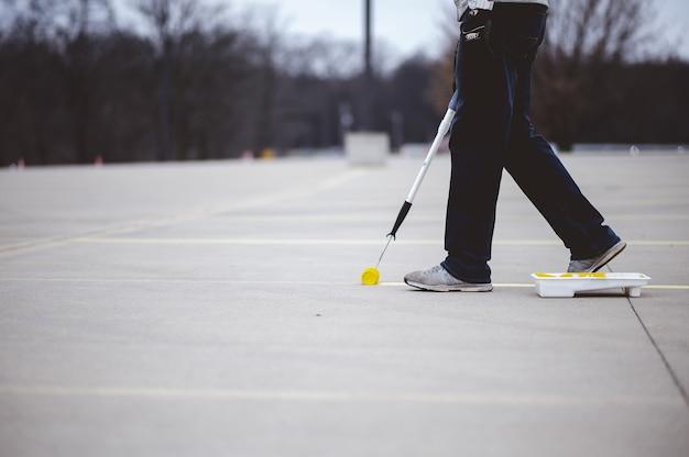 Weergave van een persoon die de parkeerlijnen op het asfalt van een parkeerplaats opnieuw schildert met gele verf Gratis Foto