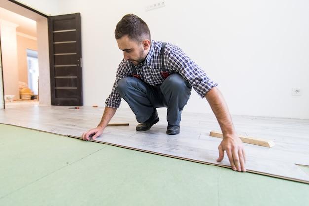 Weergave van jonge werknemer tot een vloer met laminaatvloer planken sluit Gratis Foto