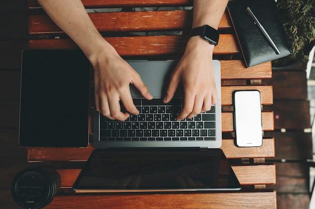 Weergave van mannelijke handen bijsnijden met behulp van laptop staande op houten plank tafel met gadgets en notebook van bovenaf rondslingeren Premium Foto