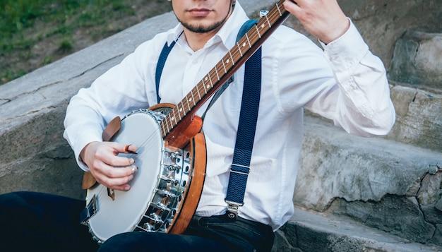 Weergave van muzikant banjo spelen op straat Premium Foto