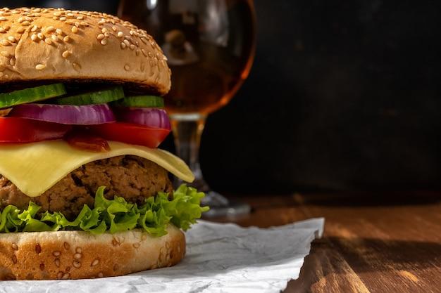 Weergave van verse smakelijke hamburger met glas bier op houten rustieke tafel. Premium Foto