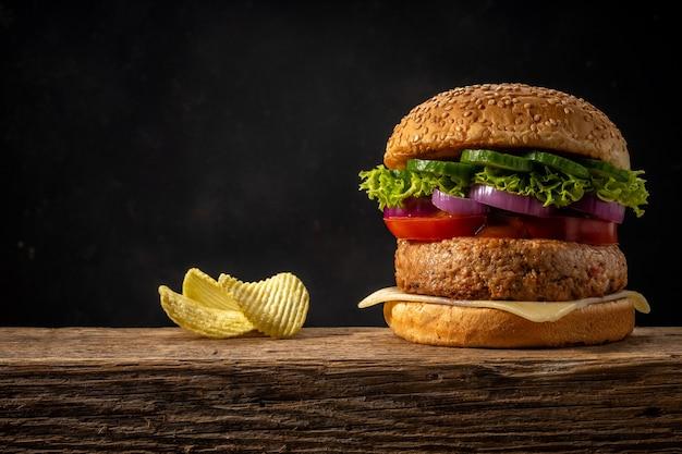 Weergave van verse smakelijke hamburger op houten rustieke tafel. Premium Foto