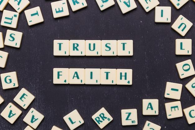 Weergave van vertrouwen en geloof scrabble letters van bovenaf Gratis Foto