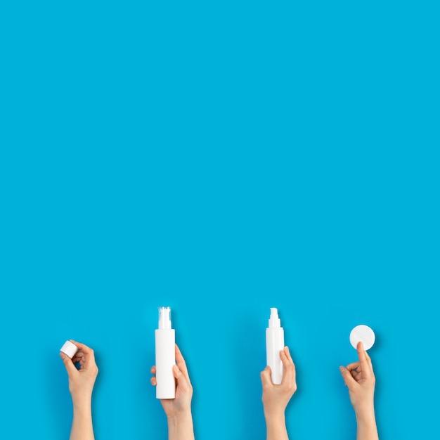 Weergave van vrouw handen met cosmetica in buizen, dispensers, flessen en pot geïsoleerd op de achtergrond Premium Foto