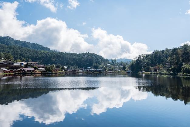 Weerspiegeling van de hemel van het kleine stuwmeer in het landelijke dorp. Premium Foto